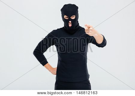 Mad irritated young man in balaclava standing and pointing on you