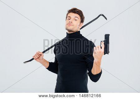 Confident young man burglar posing with gun and crowbar