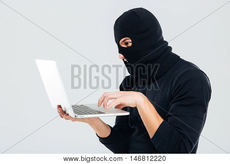 Portrait of man in balaclava standing and using laptop
