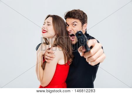 Furious criminal young man holding scared young woman and pointing with gun on you