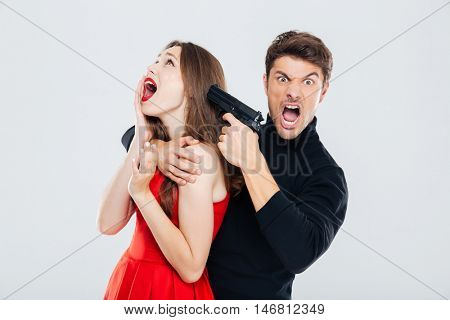 Portrait of irritated criminal young man threatening to woman with gun