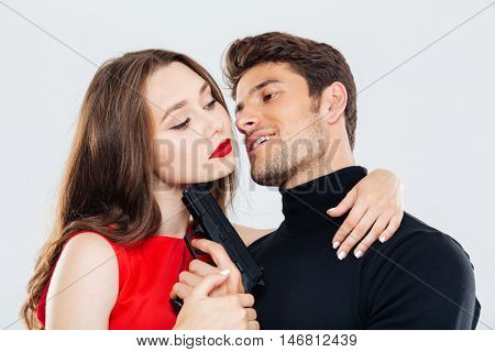 Sensual young couple hugging and posing with gun