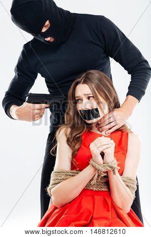 Cryminal man in balaclava threatening by gun to scared woman