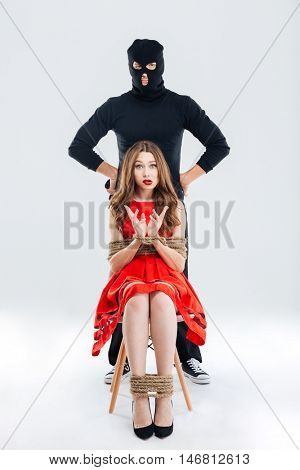 Ful length of man in balaclava and frightened young woman sitting bounded with ropes