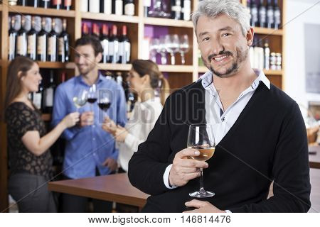 Man Holding Wineglass While Friends Communicating In Shop