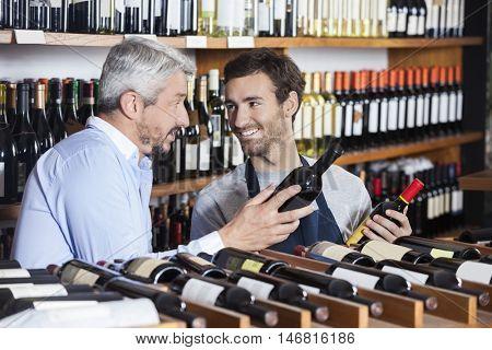 Salesman And Customer Holding Wine Bottles