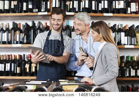 Salesman Showing Wine Information To Couple On Digital Tablet