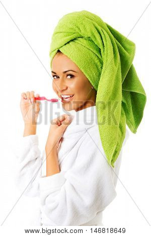 Woman in bathrobe brushing teeth