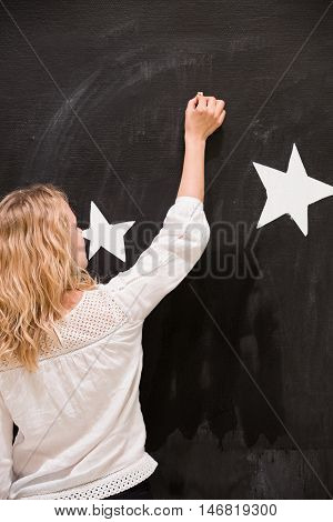 Back view on blond woman teacher writing with chalk on a black board with white stars. Girl drawing on the black wall in the classroom. Creativity activities for children indoors