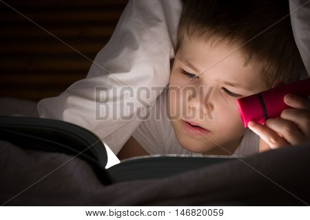 Small kid boy with a smile hiding under a blanket and reading a book with his flashlight in his bedroom at night. Enjoying learning and books.