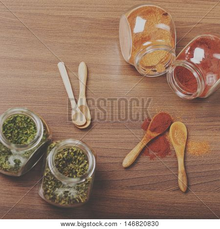 Four glass jar with spices and four wooden spoon on the table