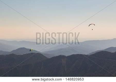 Paragliders flying over a scenic mountainous landscape