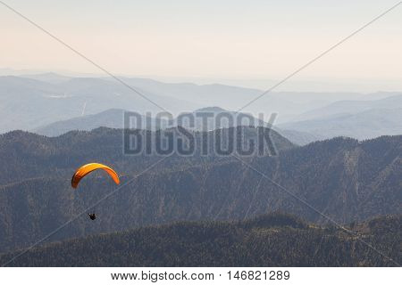 Paraglider flying over a scenic mountainous landscape