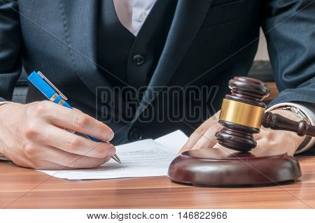 Lawyer Is Writing On Document. Wooden Gavel In Front.