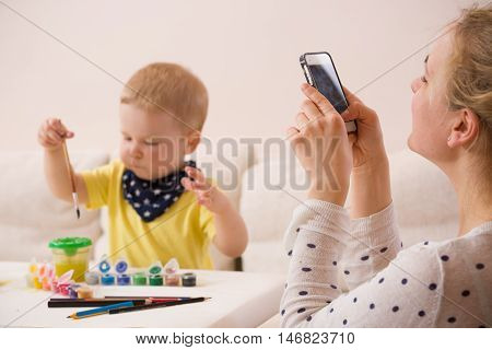 Young mother taking photo of cute little toddler boy in yellow shirt sitting at table and drawing with colorful paints. Early learning. Creative. Toddler drawing. Mom making picture on mobile phone