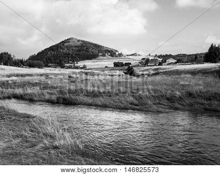 Conical mountain Bukovec above Jizerka village and Jizerka creek, Jizera Mountains, Czech Republic . Black and white image.