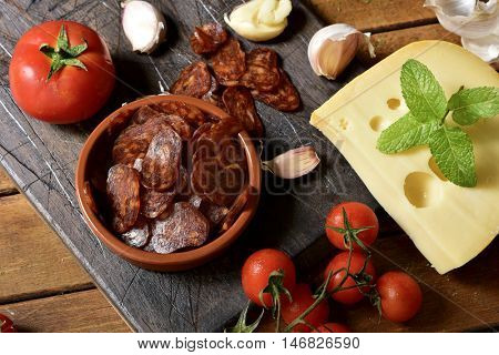 high-angle shot of an earthenware bowl with some slices of Spanish chorizo, a pork sausage typical of Spain, on a rustic wooden table next to a piece of cheese, some tomatoes and garlic cloves