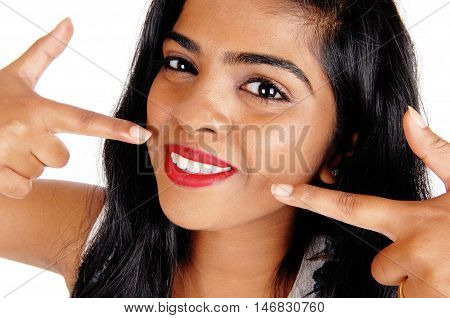 A closeup image of the face and white teeth of a beautiful young woman isolated for white background.