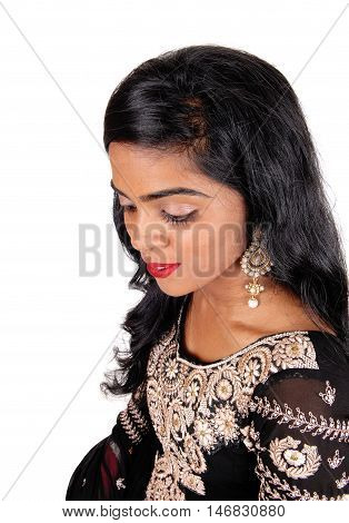 A gorgeous young Indian woman in a original Indian dress and long black hair standing in profile isolated for white background.