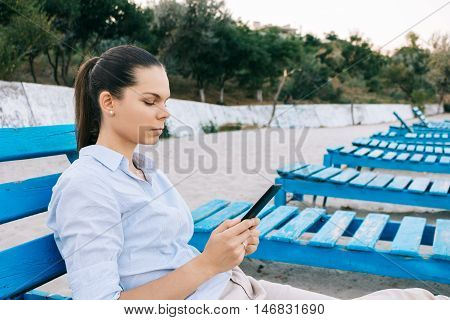 Side View Of A Young Woman On The Beach Reading A Book Sitting On The Bench
