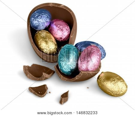 Broken chocolate Easter egg with colorful candies on white background