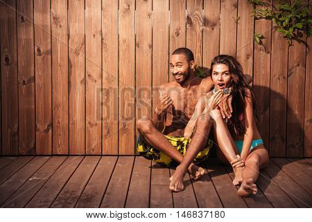 Happy cheerful mixed race couple showing thumbs up over wooden background