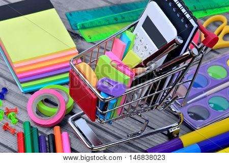Many objects school with shopping cart on wooden table
