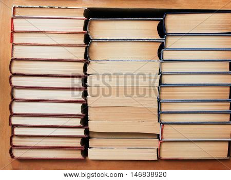 Stacks of different books in good condition on the shelf in the library ready to read