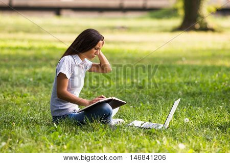 Worried businesswoman sitting at the park and working.