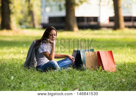 Businesswoman is sitting in the park and she is sad and worried because she has spent too much money.