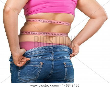 Female who has gained weight and can no longer fit into her jeans - isolated image