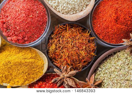 Spices and herbs in metal  bowls and wooden spoons. Food and cuisine ingredients