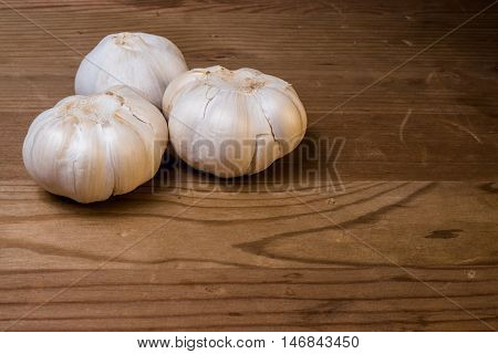 Garlic cloves on a wood surface ready to be chopped and cooked