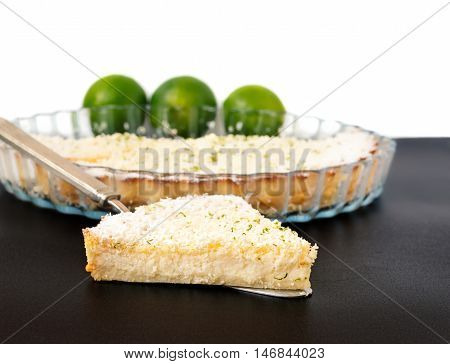 Lemon lime coconut impossible pie with white chocolate shavings slice on a silver cake server with limes and dish in the background