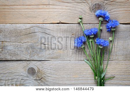Blue cornflowers on wooden background top view