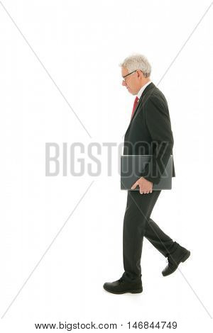 Formally dressed Senior business man walking with laptop