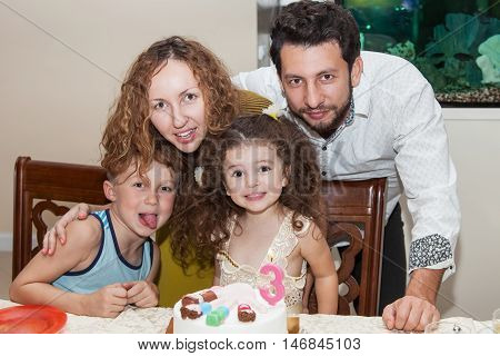 Happy family of four persons birthday celebration happy little birthday girl sitting at table with birthday cake elder brother showing tongue