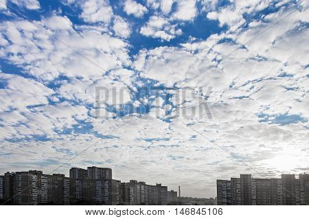 Evening blue sky with white clouds just before sunset buildings on horizon the city of Kiev Ukraine