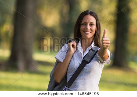 Beautiful businesswoman is standing in the park and showing thumb up.