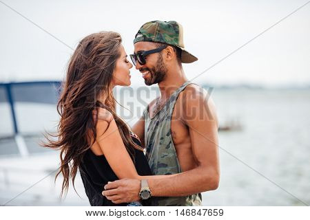 Portrait of romantic young beautiful couple in love embracing at the pier