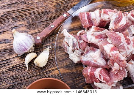 diced bacon raw meat in a plate on a wooden board