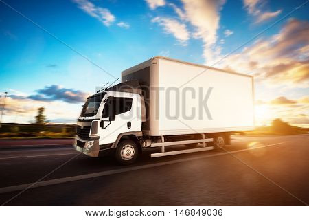 Commercial cargo delivery truck with blank white trailer driving on highway. Generic, brandless vehicle design. 3D rendering