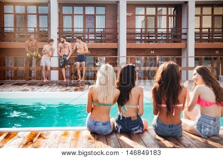 Back view of attractive young women sitting near swimming pool and looking at attractive men in shorts