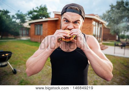 Young bearded hipster guy biting delicious burger outdoors