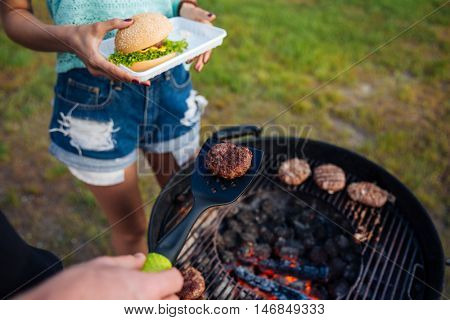 Top view of young people cooking meet on barbeque grill and making hamburger outdoors