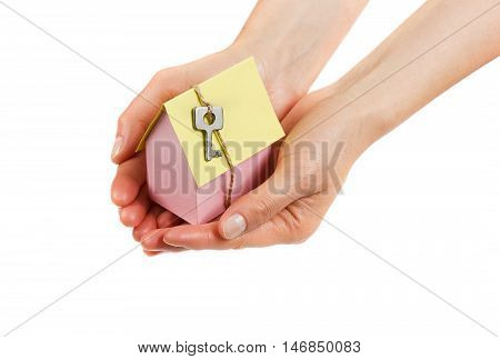 Woman hands holding a model of cardboard house with key on twine isolated on white background. House building, loan, real estate or buying a new home concept.