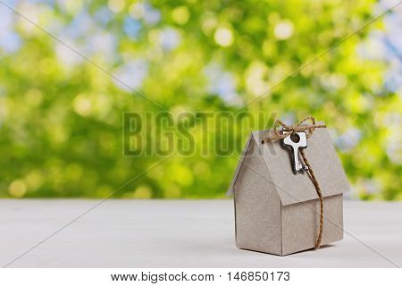 Model of cardboard house with a bow of twine and key against green bokeh background. Building, loan, real estate or buying a new home concept.