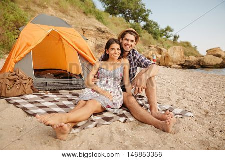 Young happy beautiful couple sitting at the tent at the beach