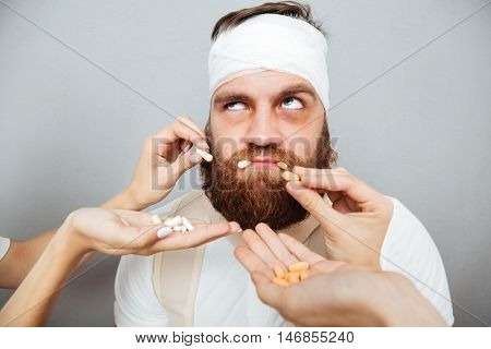 Unhappy irritated young man taking pills from doctors hands over gray background