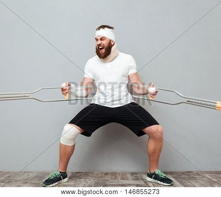 Crazy bearded young man holding and playing with crutches over white background